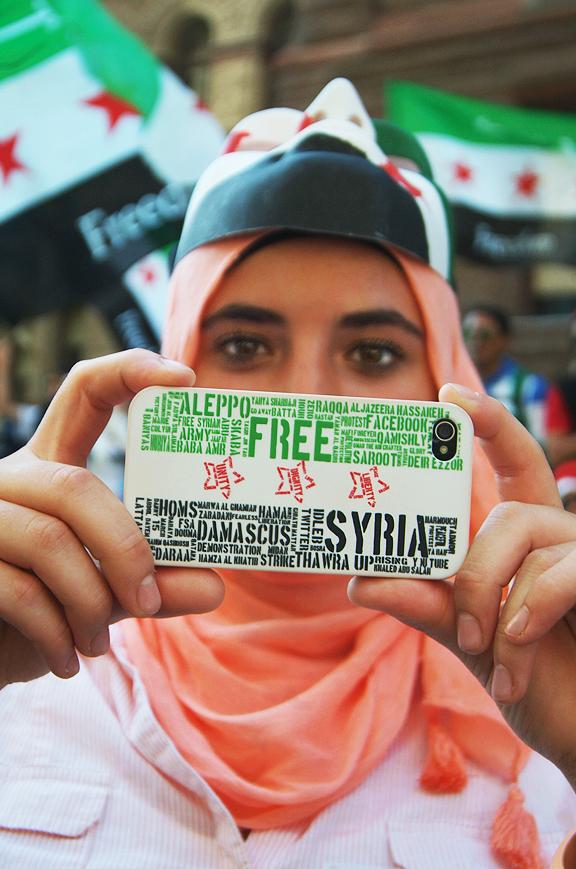Syrerin mit Handy auf Demo