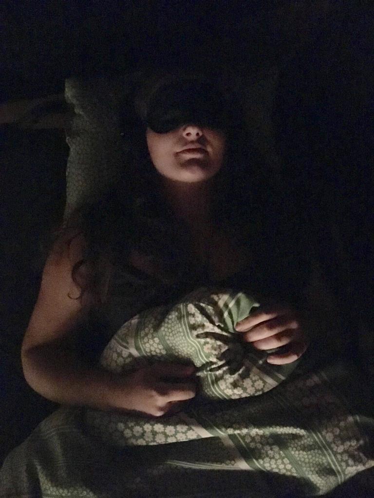Frau mit Augenbinde und Kopfhörern im Bett