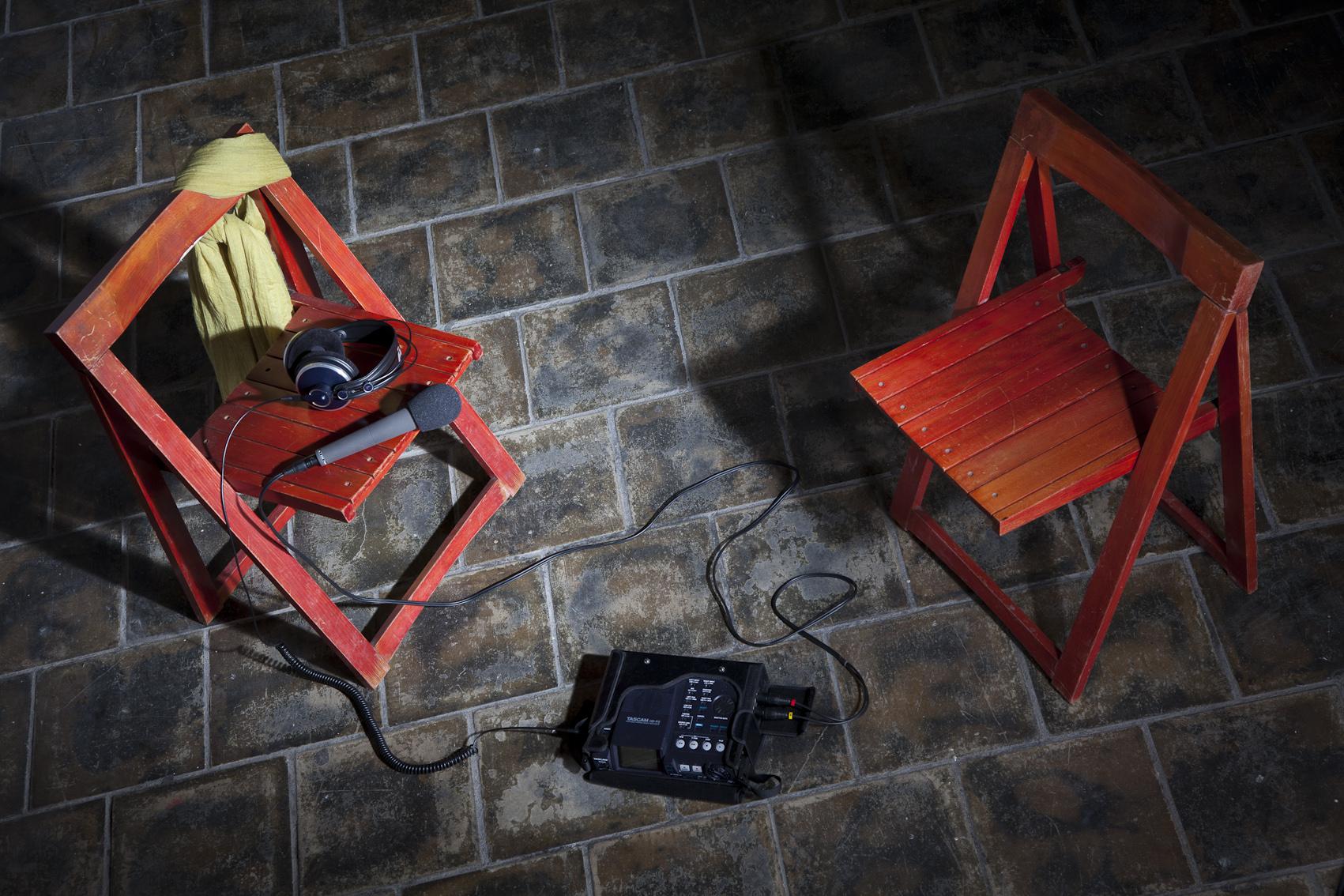 Zwei Stühle mit Mikrofon, Kopfhörern, Aufnahmegerät, Augenbinde