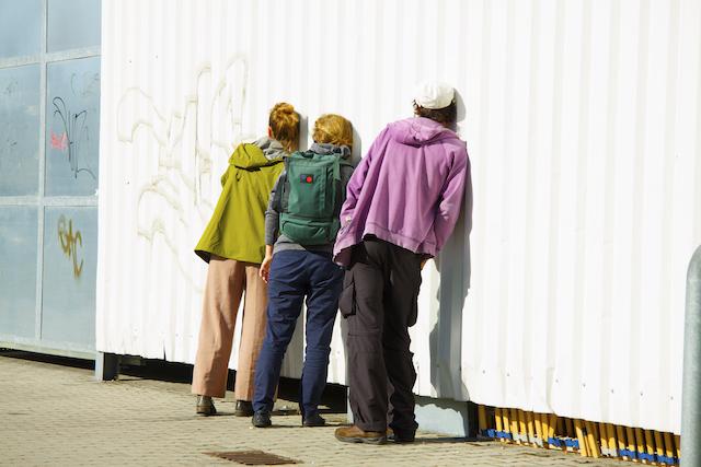Drei Menschen lauschen an einer Metallwand
